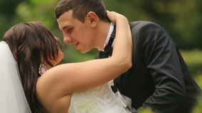 Cheerful newlyweds embracing, in green summer park. Handsome groom gently tilts and kisses his lovely bride stock video footage