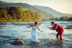 Cheerful newlyweds are having fun in the river. The groom is splashing water on his beautiful smiling bride during the. Sunset Royalty Free Stock Photography