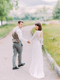 The cheerful newlyweds are holding hands during their walk. Stock Image