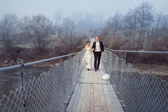 Cheerful newlyweds walking and laughing on the wooden bridge. Honeymoon at mountains Stock Photos