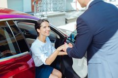 Cheerful nice businesswoman getting out of the car Stock Photos