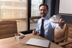 Cheerful nice man offering you a cup of coffee Royalty Free Stock Image