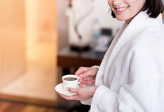 Cheerful nice woman drinking coffee. Unforgettable taste. Cheerful delighted smiling woman sitting on the bed and drinking coffee while expressing gladness royalty free stock photos