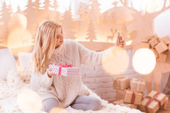Cheerful nice woman taking a selfie with her present Stock Photography