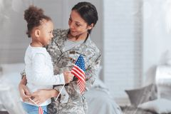 Cheerful nice woman wearing a military uniform. Patriotic family. Cheerful nice pleasant women wearing a military uniform and looking at her daughter while stock photography