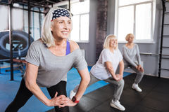 Cheerful nice women visiting aerobic classes. Being active. Cheerful sporty aged women smiling and doing physical exercises while visiting aerobic classes royalty free stock photos