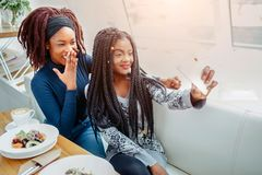 Cheerful nice young african women in cafe. They take selfie on phone camera. Models smile. They sit at table. stock images