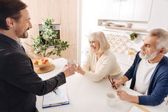 Cheerful notary having meeting with senior couple of clients Royalty Free Stock Image
