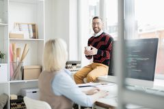 Cheerful office man drinking coffee while talking to coder. Cheerful excited handsome office men in stripped sweater sitting on window sill and drinking coffee stock image