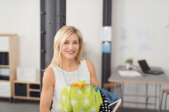 Cheerful Office Woman Holding her Other Clothes Stock Photo