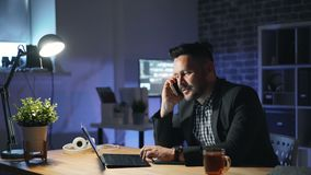 Cheerful office worker chatting on phone and working with laptop in dark office stock footage