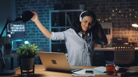 Cheerful worker listening to music dancing working with laptop in dark room stock video