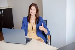 Cheerful office-worker showing thumbs up in front of laptop.  royalty free stock photos