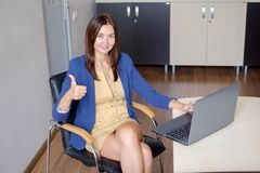 Cheerful office-worker showing thumbs up in front of laptop.  royalty free stock photo