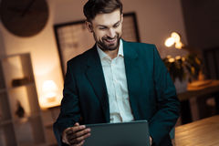 Cheerful office worker spending time with pleasure. Watching video. Positive delighted male bowing head while looking at screen of computer and sitting in his Stock Image