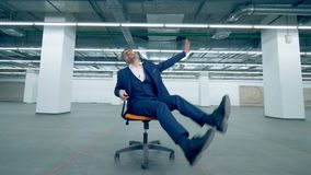 Cheerful office worker spinning on a chair, fun activity. 4K stock video footage
