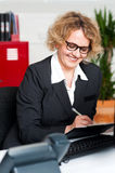 Cheerful office worker writing notes Royalty Free Stock Photography