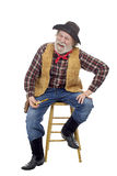 Cheerful old cowboy sits holds corn cob pipe Royalty Free Stock Images