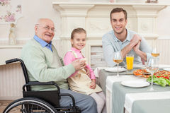Cheerful old disabled grandfather with his family. We are happy together.  Senior men is celebrating birthday with his son and granddaughter at home. They are Royalty Free Stock Photos