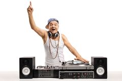 Cheerful old DJ playing music on  a turntable and holding his fi Royalty Free Stock Photography