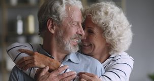Cheerful old couple hugging laughing bonding looking at camera
