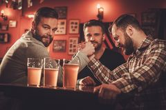 Cheerful old friends having arm wrestling challenge in a pub. Royalty Free Stock Photography