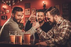 Cheerful old friends having arm wrestling challenge in a pub. Royalty Free Stock Image