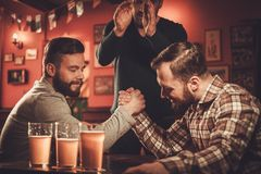 Cheerful old friends having arm wrestling challenge in a pub. Royalty Free Stock Photo