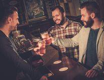 Cheerful old friends having fun and drinking draft beer at bar counter Royalty Free Stock Images