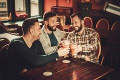 Cheerful old friends having fun and drinking draft beer in pub. Royalty Free Stock Photo