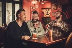Cheerful old friends having fun and drinking draft beer in pub. Royalty Free Stock Photos