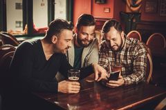 Cheerful old friends having fun and drinking draft beer in pub. royalty free stock image