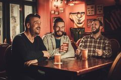 Cheerful old friends having fun and drinking draft beer in pub. stock image