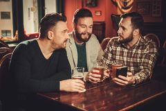 Cheerful old friends having fun and drinking draft beer in pub. stock photo