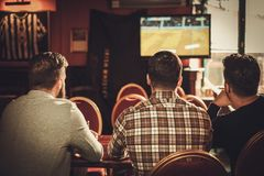 Cheerful old friends watching sports and drinking draft beer in pub. Stock Photo