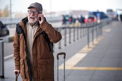 Cheerful old gentleman in glasses is enjoying phone communication. Deeply involved in conversation. Portrait of joyful senior man with beard is resting on Stock Photography