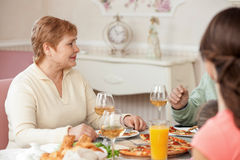 Cheerful old lady is dining with her relatives Stock Photos