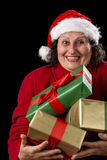 Cheerful Old Lady Offering Three Wrapped Gifts. Delighted female pensioner with Santa Claus cap and red coat is carrying three Christmas gifts close to her chest Stock Images