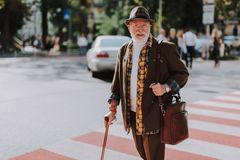 Cheerful old male walking across the street. Portrait of happy senior man going across the street with stick and holding briefcase. Copy space on left side royalty free stock photography