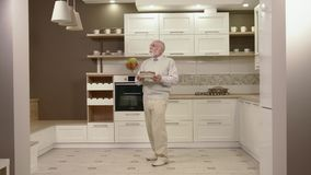 Cheerful Old Man Dancing In The Kitchen stock video footage