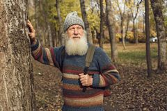 Old man with beard in forest. Cheerful old man enjoying walk near trees stock photos