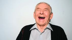 Cheerful old man is laughing heartily isolated on white background. stock video footage
