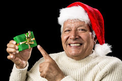 Cheerful Old Man Pointing At Green Wrapped Gift. Jolly male senior pointing at small, green, wrapped gift presented in his right hand. Red Father Christmas cap Royalty Free Stock Images