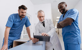 Cheerful old physician using gadget with colleagues at work Royalty Free Stock Images