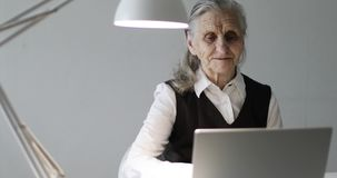 Cheerful old woman with deep wrinkles talking on the video connection. Grandma works at a laptop stock video