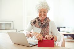 Cheerful Old Woman Getting Something from Her Wallet Royalty Free Stock Photos