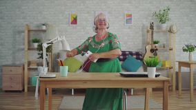 Cheerful old woman with gray hair in headphones listening to music and dancing. Cheerful happy old woman with gray hair in headphones listening to music and stock video footage