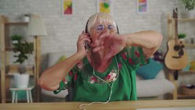Cheerful old woman with gray hair in headphones listening to music and dancing close up. Cheerful happy old woman with gray hair in headphones listening to music stock video footage
