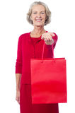 Cheerful old woman holding shopping bag Stock Photo