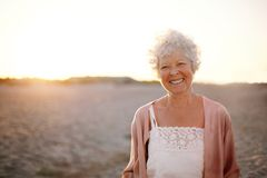 Cheerful old woman standing on the beach stock images
